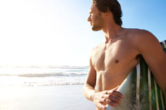 Male surfer carrying surfboard at the beach. Portrait of a male surfer carrying surfboard at the beach Stock Image