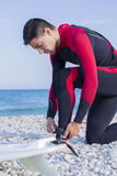 Male surfer getting ready. Young man with a wetsuit is adjusting the leash of a surf board to the ankle on the beach - focus on the left hand Royalty Free Stock Images