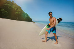 Male surfer holding surf board walking out of the sea. Shot of young male surfer holding surf board walking out of the sea. Caucasian male with surfboard walking Stock Photos