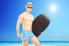 Male surfer holding a surfboard and looking at camera on a sunny. Day, on a beach Stock Image