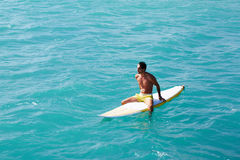 Male surfer looking at the horizon while sitting on her surfboard. Shot of a handsome young man enjoying a surf in clear blue water, male surfer in the ocean stock photo