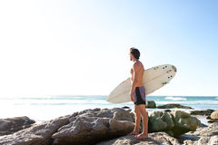 Male surfer looking at the sea. Full length portrait of male surfer looking at the sea Royalty Free Stock Images