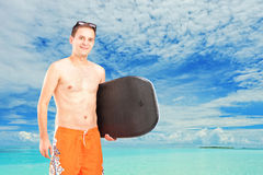 A male surfer posing with his surfboard. On a beach Royalty Free Stock Photo