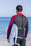 Male surfer ready to surf. Back view of a young man with a wetsuit is looking at the sea on a surf session on the beach - focus on the neck Royalty Free Stock Photo