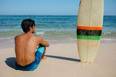 Male surfer relaxing on the sea shore Stock Photos