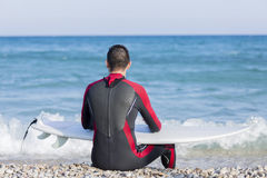 Male surfer resting. Back view of a young man with a wetsuit siting on the seashore and holding his surf board is looking at the sea - focus on the head Royalty Free Stock Image