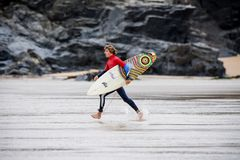 A male surfer running across the beach with surfboard. A male surfer running across a Cornwall beach with a surfboard under his arm Royalty Free Stock Photography