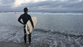 Male surfer at sunset. A male surfer is standing on the beach near sunset, holding his surfboard and looking at the waves Stock Photos