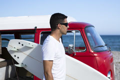 Male surfer and a surf board. Young man is holding a surfboard next to a classic van looking at the sea on a session on the beach - focus on the face Stock Photos