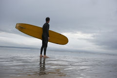 Male Surfer With Surfboard Looking At Sea On Beach. Full length of young male surfer with surfboard looking at sea on beach Stock Photography