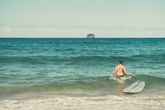 Male Surfer with Surfboard in Ocean Royalty Free Stock Photography