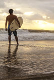 Male Surfer & Surfboard Sunset Sunrise Beach. Rear view of male surfer with white surfboard standing on a beach at sunset or sunrise Royalty Free Stock Images