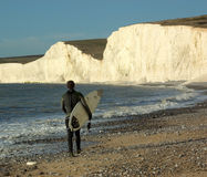 Surfer at the beach. A male surfer walking along the beach close to the Seven Sisters range of chalk cliffs Royalty Free Stock Photos