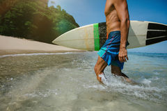 Male surfer walking out of the ocean. Cropped shot of young male surfer holding surf board walking out of the ocean. Caucasian male with surfboard coming out of Stock Photos
