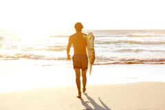 Male surfer walking into water. Portrait from behind of male surfer walking into water Stock Photography