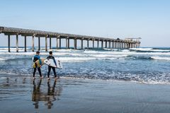 Male Surfers Carrying Surfboards Head Out to Sea Near Scripps Pier. LA JOLLA, CALIFORNIA/USA - APRIL 28, 2018:  Two male surfers carrying surfboards heads out to Royalty Free Stock Image