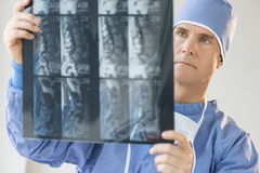 Male Surgeon Examining X-Ray Report. Mature male surgeon examining X-ray report in hospital Stock Images