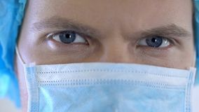 Male surgeon face in mask looking confidently closeup, reliable medical services stock photography
