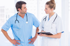 Male surgeon and female doctor with medical reports. At the hospital Stock Image