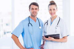 Male surgeon and female doctor with medical reports. Portrait of a male surgeon and female doctor with medical reports at the hospital Royalty Free Stock Photo