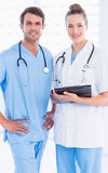 Male surgeon and female doctor with medical reports Stock Photos