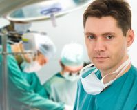 Male surgeon with his team. Male surgeon with two doctors on background in operation room Stock Image