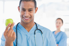 Male surgeon holding an apple with colleague behind. Smiling male surgeon holding an apple with colleague behind at a bright hospital Royalty Free Stock Images