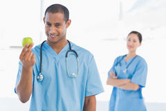 Male surgeon holding an apple with colleague behind. Smiling male surgeon holding an apple with colleague behind at a bright hospital Stock Photos