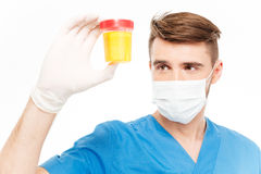 Male surgeon holding bottle of urine sample. Male surgeon with mask holding bottle of urine sample isolated on white background Royalty Free Stock Images