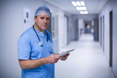Male surgeon holding digital tablet. Portrait of male surgeon holding digital tablet at hospital Royalty Free Stock Images