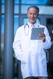 Male surgeon holding digital tablet. Portrait of male surgeon holding digital tablet at hospital Stock Images