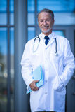 Male surgeon holding file. Portrait of male surgeon holding file at hospital Stock Image