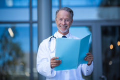 Male surgeon holding medical report. Portrait of male surgeon holding medical report file at hospital Stock Image