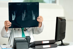 Male surgeon holding x-ray. Which hid his face Stock Photography