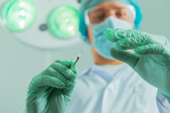 Male surgeon holds a scalpel. Man surgeon holds a scalpel in an operating room, focus on scalpel Stock Image