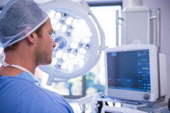 Male surgeon looking at patient monitoring machine in operation theater. At hospital Stock Photography