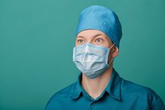 Male surgeon in mask on blue background, close up Stock Photo