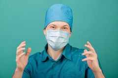 Male surgeon in mask looking at camera on blue background, close up Royalty Free Stock Image