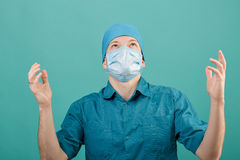 Male surgeon in mask looking at camera on blue background, close up Royalty Free Stock Photography
