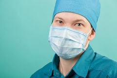 Male surgeon in mask looking at camera on blue background, close up Stock Photography