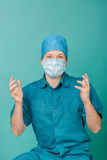 Male surgeon in mask looking at camera on blue background, close up Stock Photos