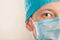 Male surgeon in mask looking at camera on grey background, close up Stock Photography