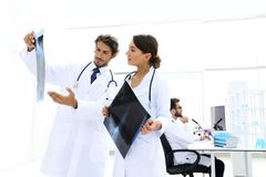 Male surgeon with nurse examining x-ray report. Shot of a female doctor, analyzing an X-ray examination of a patient with colleagues Stock Image