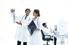 Male surgeon with nurse examining x-ray report. Shot of a female doctor, analyzing an X-ray examination of a patient with colleagues Stock Photography