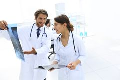 Male surgeon with nurse examining x-ray report. Shot of a female doctor, analyzing an X-ray examination of a patient with colleagues Royalty Free Stock Photography