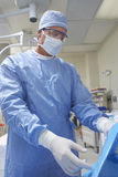 Male Surgeon In Operating Room. Male surgeon in protective workwear preparing for operation Stock Photo