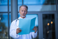 Male surgeon reading medical report. At hospital Stock Images