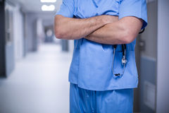 Male surgeon standing with arms crossed. Mid section of male surgeon standing with arms crossed at hospital Royalty Free Stock Photo