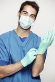 Male surgeon takes on gloves. Studio shot Stock Photo