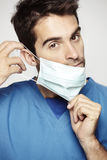 Male surgeon takes on his mask. Studio shot Stock Images